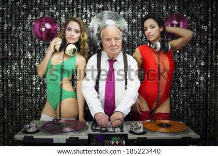amazing grandpa DJ and his two beauitful gogo dancers - stock photo