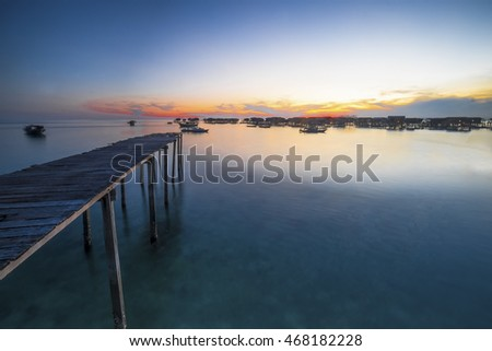 Amazing hue of colourful Mabul Island Sabah in sunset moment with silhouette of sea house. motion of the clouds and wave are observed due to long exposure shot. nature composition