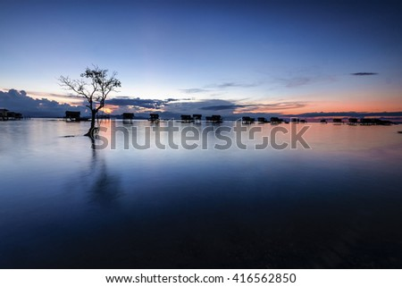Amazing hue of seascape view during sunset hour in Bogaya Island in Sabah Malaysia. motion of the clouds and wave are observed due to long exposure shot. nature composition - stock photo