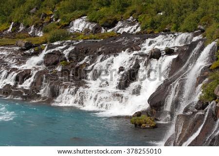 Amazing Icelandic waterfall Hraunfossar. Water is flowing through lava field. - stock photo