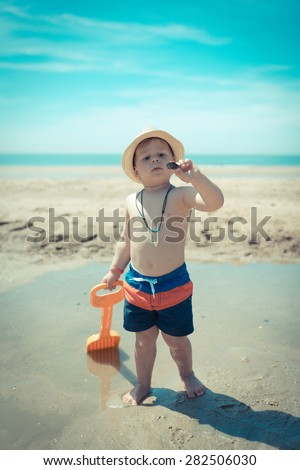 amazing kid looking at a shell on the beach - stock photo