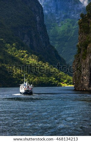 Amazing landscape of nature. Natural wonders, mountains, fjords and forests. Colors seem very beautiful. A big fishing boat sailing between mountains. Flam, Norway