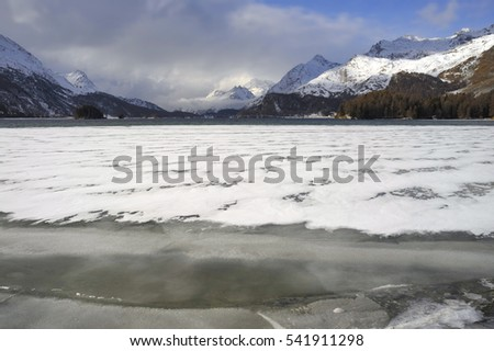 amazing landscape scenic view of Engadin valley in Switzerland Sils Maria village with snow on Alp mountains and frozen lake on a cold sunny winter day in tourism and holiday destination