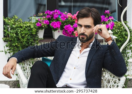 amazing man in a jacket and shirt sitting on a chair and looking forward, flowers background