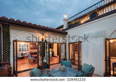 Amazing Mediterranean home at twilight with patio and open french doors. Spanish style home at twilight and open floor plan. - stock photo