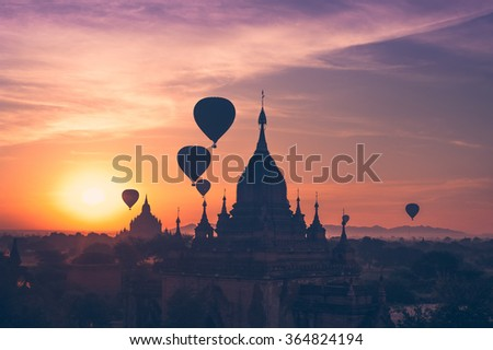 Amazing misty sunrise colors and balloons silhouettes over ancient Dhammayan Gyi Pagoda. Architecture of old Buddhist Temples at Bagan Kingdom. Myanmar (Burma). Travel landscapes and destinations - stock photo