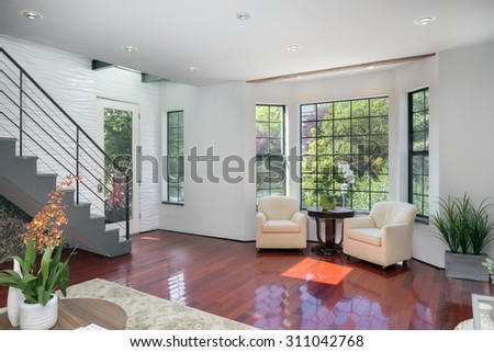 Amazing modern interior with seating arrangement, staircase, glass entry door and cherry wooden flooring. - stock photo