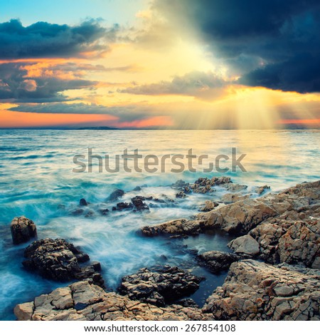 Amazing morning sun over the sea with overcast sky. - stock photo