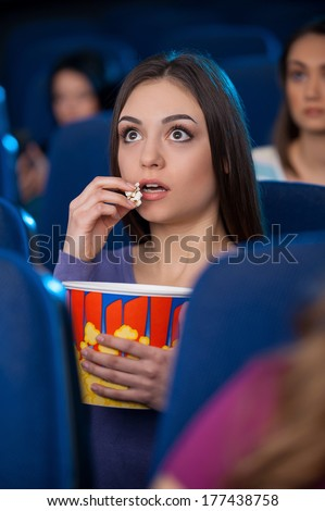 Amazing movie! Excited young woman eating popcorn and watching movie while sitting at the cinema  - stock photo