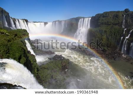 Amazing National Park of Iguazu Falls with a full rainbow over the water, Foz do Iguaçu, Brazil - stock photo