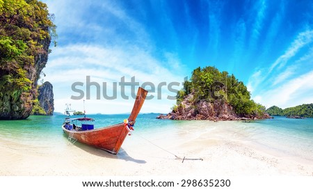 Amazing nature and exotic travel destination in Thailand. Thai tourist boat on white sand beach of small tropical island - stock photo