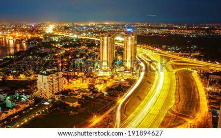 Amazing nightscape of Ho chi Minh city, Vietnam from high view, city bright in yellow electric light, trail on road, landscape of new urban in radiant colors at night