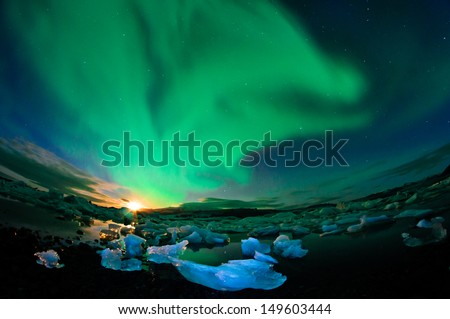 Amazing northern lights performance over glacier lagoon in Iceland during setting moon - stock photo