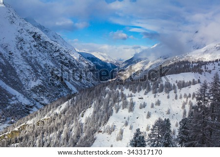 Amazing panoramic view on Matterhorn - famous mountain in Swiss Alps, with aerial view on Zermatt Valley, Switzerland, in a sunny winter day, with blue sky, clouds and view on Zermatt ski resort