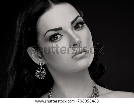 Amazing portrait eastern woman face, has big fairy eyes, beautiful brunette hair, sexy lips, long eyelashes, silver necklace and earrings jewelry. Luxury makeup. Black and white.