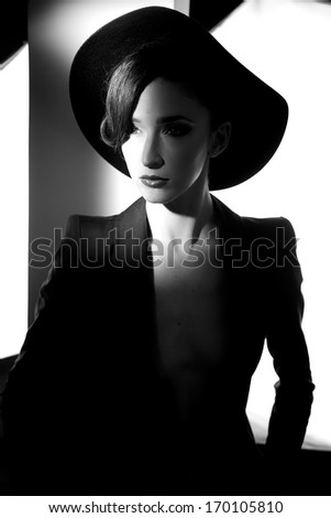 Amazing portrait of female model posing with hat and jacket black and white - stock photo