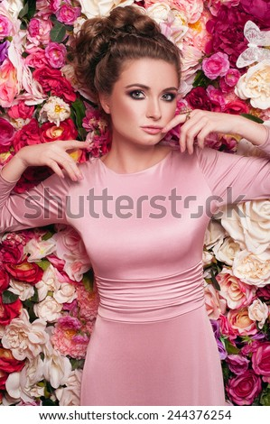 Amazing portrait of young beautiful lady in rosy skin-tight dress with charming curles and bunches, dark smoky eyes, pink lipstick with head to the right and arms near her head looking at you
