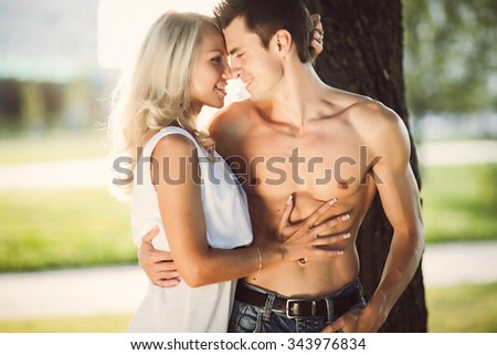 Amazing pretty couple hug and kissing outdoor,sensual people,Romantic young couple together outdoors on summer day.Caucasian couple enjoying the beach view.Enjoy time together,lovely couple  - stock photo