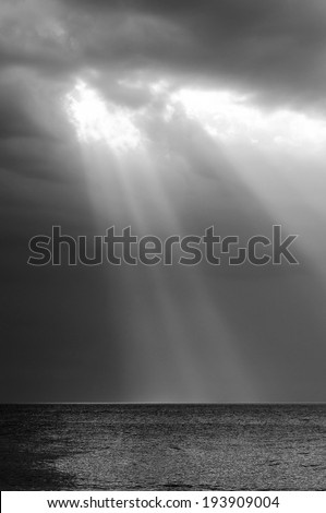 Amazing ray of light shines through storm clouds over ocean - stock photo