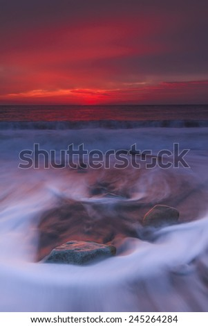 Amazing red sunset over the sea waves - stock photo