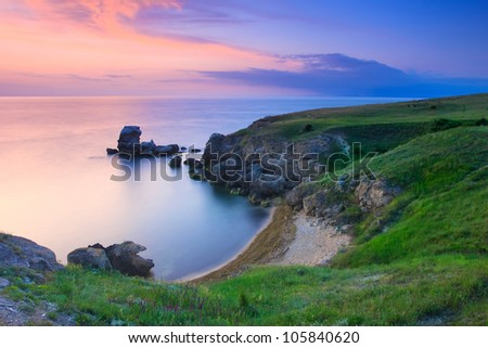 Amazing rocky coastline at sunset with the island