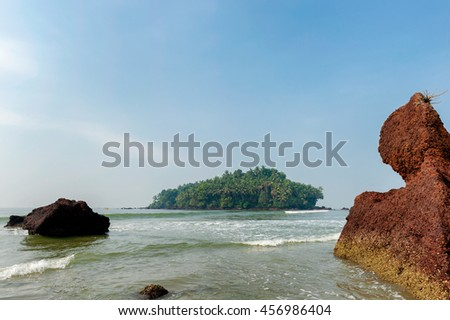 Amazing rocky shore in southern Asia and a beautiful island in the background