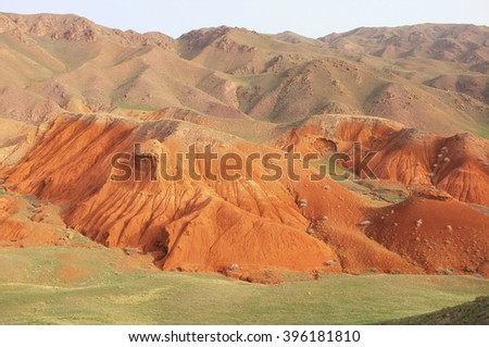 Amazing scenic orange hills, screes of sandstone, sides carved away by erosion, canyon Uchterek, Kyrgyzstan, Central Asia. - stock photo