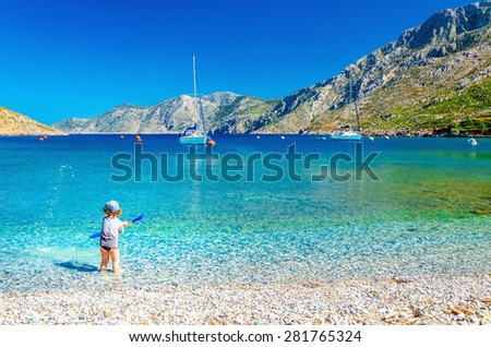 Amazing sea bay on Greek Island with a small boy at play on the seashore, Greece - stock photo