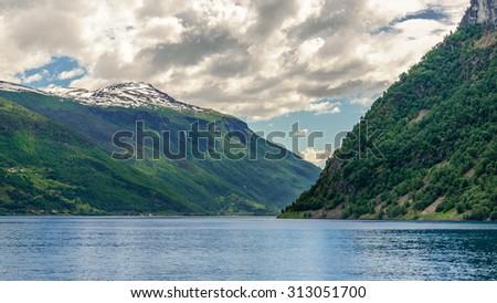 Amazing sea landscape with the blue surface of the water, magic grey clouds on the blue sky over mountain slopes with green forest, Sognefjord, Norway