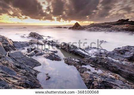 Amazing seascape during sunrise with slow shutter technique - stock photo