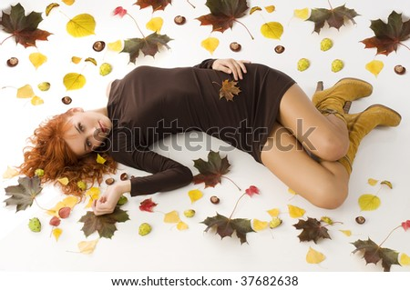 amazing shot of red haired woman laying down on white floor with autumn leaves all around