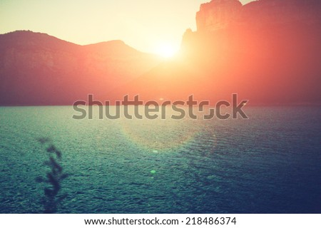 Amazing silhouette of mountains at sunset, bright sunset rays over the lake at evening, mountains and lake - stock photo