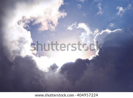 Amazing sky and cloudscape as the sun emerges among dramatic clouds. Symbol for a new day full of hope and possibilities. - stock photo