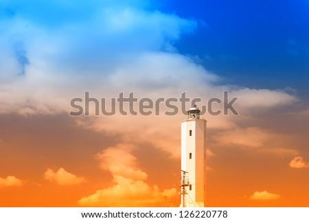 amazing sky over the lighthouse at sunrise - stock photo