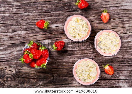 amazing strawberry cheesecake mousse cups decorated by homemade ice cream on an old rustic wooden table, top view  - stock photo