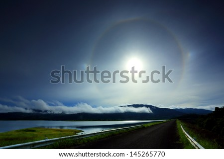 Amazing sun halo above rural road with lake and mountains - stock photo