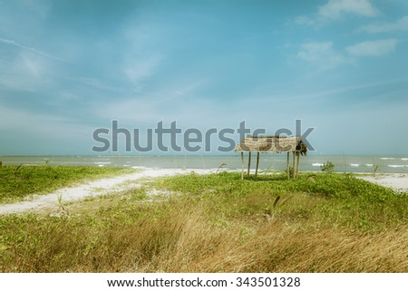 Amazing sunny day at tropical ocean beach with traditional fisherman hut near village. Myanmar (Burma) travel landscapes and destinations - stock photo