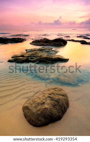 Amazing sunrise at tropical ocean with refelection and mossy rock in foreground