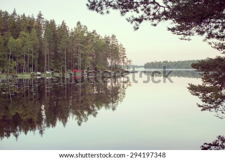 Amazing sunrise by the lake in Finland. Several boats are in the beach. Image has also a vintage effect applied.