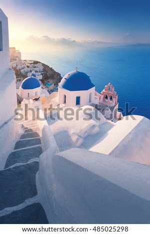 Amazing sunrise view with white houses in Oia village on Santorini island in Greece.