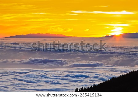Amazing sunset at the peak of volcano Teide, Tenerife, Canary Islands, Spain. Aerial view over clouds above ocean water with last sunshine . - stock photo