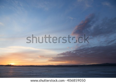 Amazing sunset by the frozen lake. Some ice is on the lake surface while sun is going down behind the forest. Some clouds are in the sky. Image taken in Finland during spring time. - stock photo