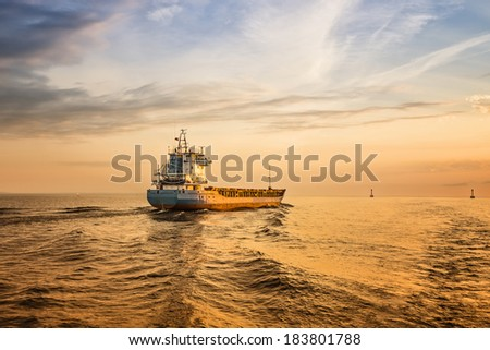 Amazing Sunset. Container ship is sailing along the waterway during sunset. Container  ship, colorfull sky and sea surface, dramatic blue dark sky.  - stock photo