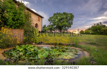 Amazing sunset in Tuscany with small pond in the foreground