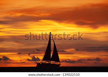 Amazing sunset landscape and sailing ship on the ocean