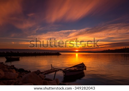 Amazing sunset on the bay with reflection and boat.