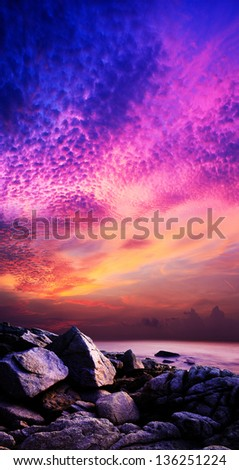 Amazing sunset over the rocky coast. Vertical panoramic composition. - stock photo