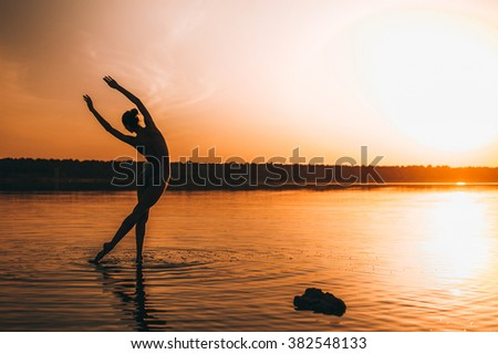 Amazing sunset portrait of the silhouette dancer. Graceful slender ballerina dancing in water, beautiful slim body, nice fit legs. Both arms and a leg lifted up.