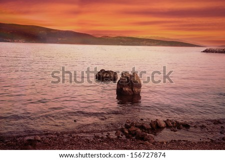 Amazing sunset sea view with single rocks and distant mountains - stock photo
