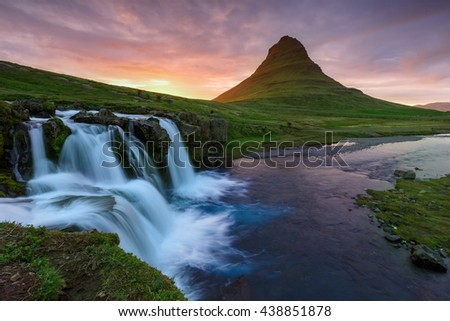 Amazing sunset the top of Kirkjufellsfoss waterfall with Kirkjufell mountain in the background on the north coast of Iceland's Snaefellsnes peninsula taken white a long shutter speed. - stock photo
